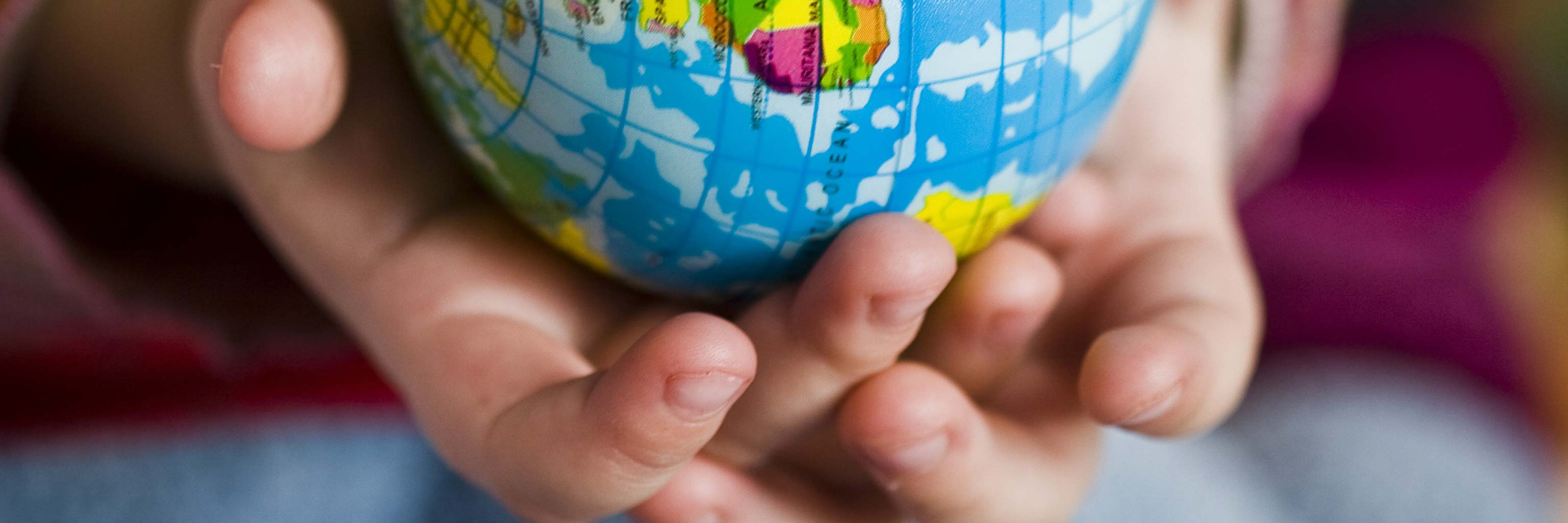 A pair of hands holding a small model of a globe