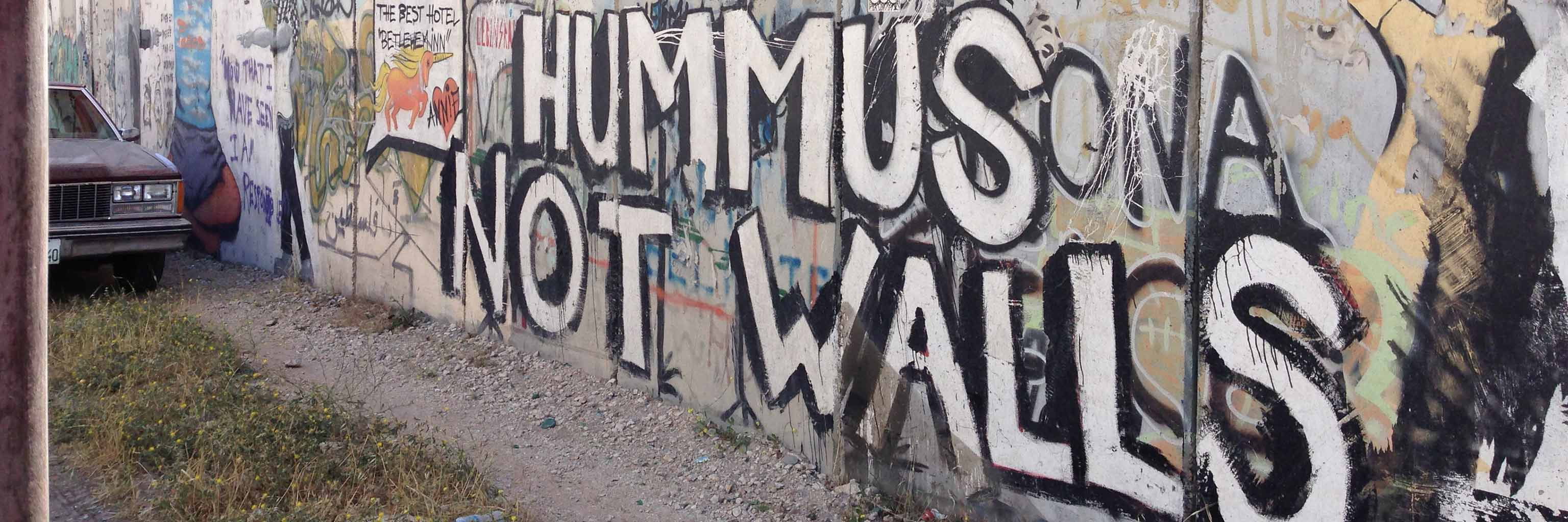 Make hummus not walls; A graffiti-covered stone wall, with a car parked against